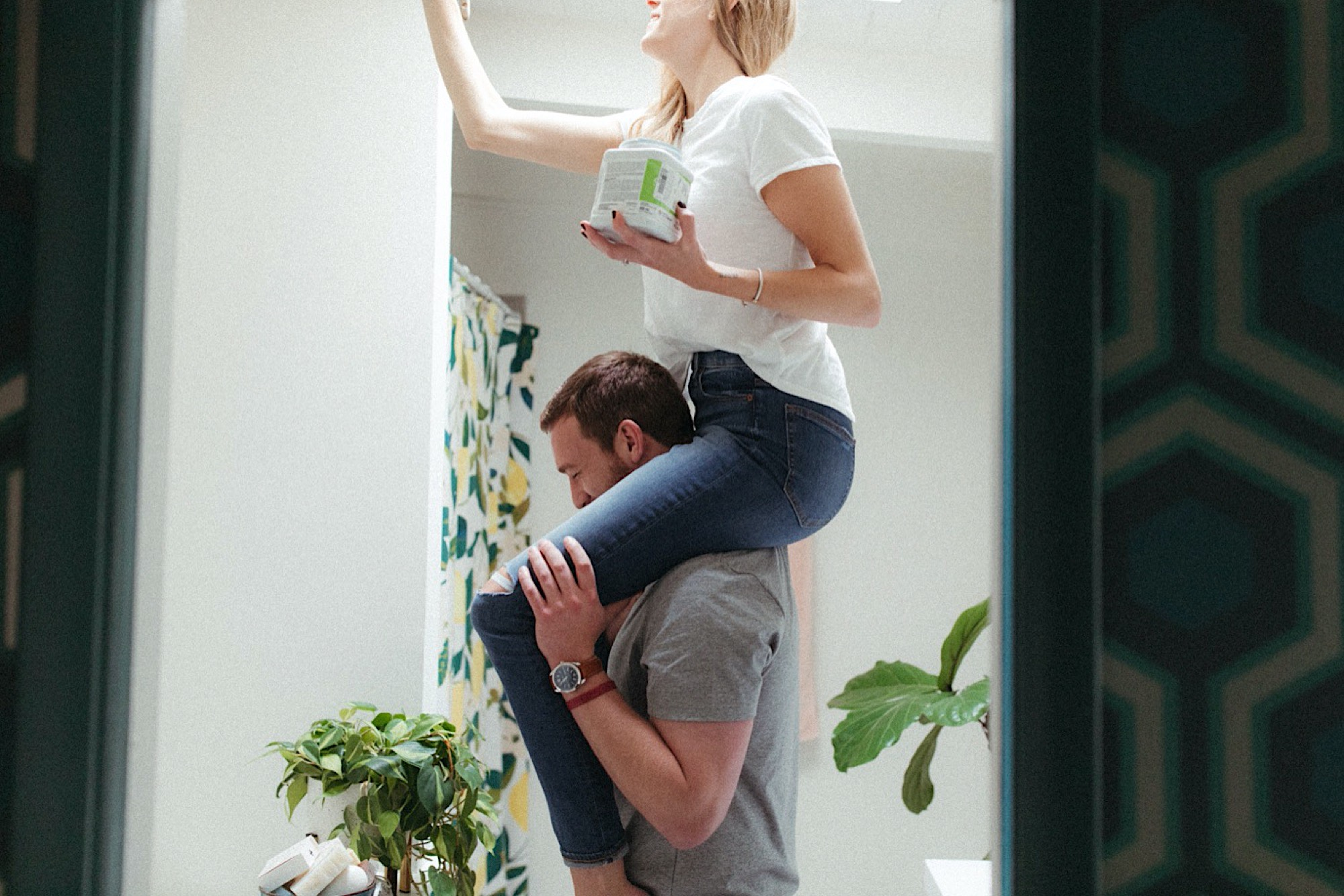 A cozy at-home Des Moines engagement couple painting bathroom